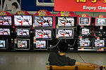 A man watches the torch run relay on several television sets at the Wal-Mart Supercenter in Beijing, China on Tuesday, August 5, 2008. The city of Beijing is gearing up for the opening ceremonies of the Olympic Games.  Kevin German