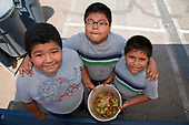 Young boys collect food for the worm compost bin after their class mates eat their lunch at the Downtown Value School.