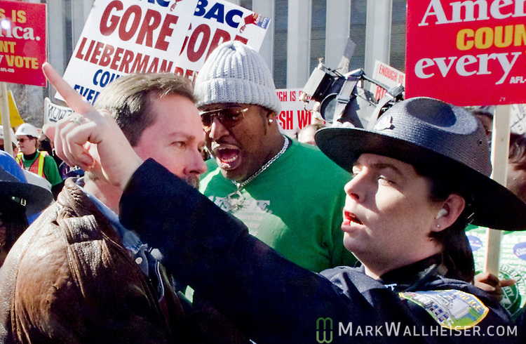 "A Florida Capitol Police Officer throws out Bush supporter from a Gore rally as the two factions collided in the Capitol plaza.  Once the Bush supporters started chanting and waving their signs, the Gore supporters, especially the AFL-CIO teamsters moved immediately to block the ""disruption"" untill law enforcement seperated to two factions arguing over the presidential voting differences in Tallahassee, Florida December 5, 2000."