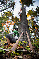 Lead mountain bike trail builder Aaron Rogers and trail building hand tools lean against a large pine tree in Copper Harbor Michigan Michigan's Upper Peninsula.