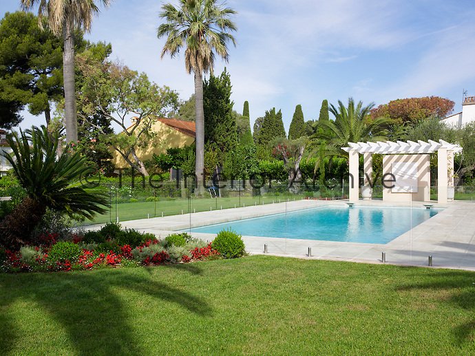 The outdoor swimming pool of a house in Cap d'Antibes is fringed by lawns and palm trees