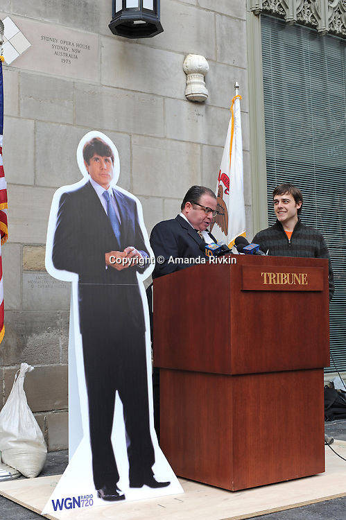 """A cardboard cut-out of former Illinois Governor Rod Blagojevich stands beside actor Neil Giuntoli playing the role of late Chicago Mayor Richard J. Daley and Kevin Floyd, 30, winner of The Chicago Tribune's contest to name Blagojevich's memoirs, outside the Tribune Tower in Chicago, Illinois on March 6, 2009. Kevin Floyd, 30, is to be awarded a beef tongue for his winning entry, Rod and the Giant Impeach, after his entry surged ahead in the final minutes the online contest was open, leading Kass to speculate on Chicago-style election tactics in his column; the beef tongue was awarded """"in symbolic anticipation"""" that the former governor will """"sing to the feds."""""""