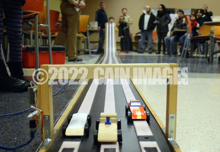 Pinewood derby cars race along a test track as the Society of Bucks Engineers, and members of Cub Scout Pack 46 discuss the best way to construct and race a small model car made out of a block of pine wood Friday, February 20, 2015 in Newtown, Pennsylvania. (Photo by William Thomas Cain/Cain Images)