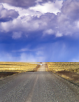 Lone road with car and thunderstorm. Near Hart Mountain, Oregon