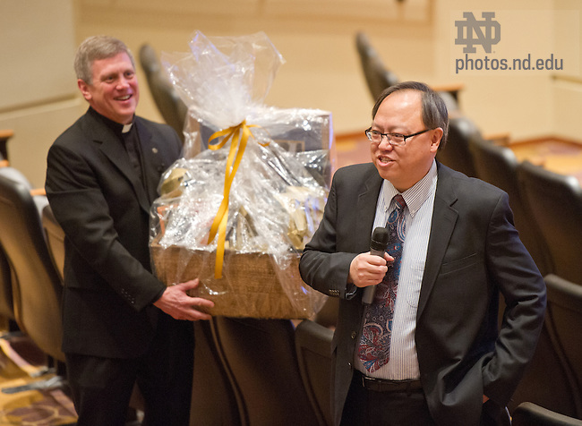 Mar. 1, 2013; Rev. Mark Theising, C.S.C. presents a gift to Mendoza College of Business Dean Roger Huang after Haung was introduced as the new Dean of the college...Photo by Matt Cashore/University of Notre Dame