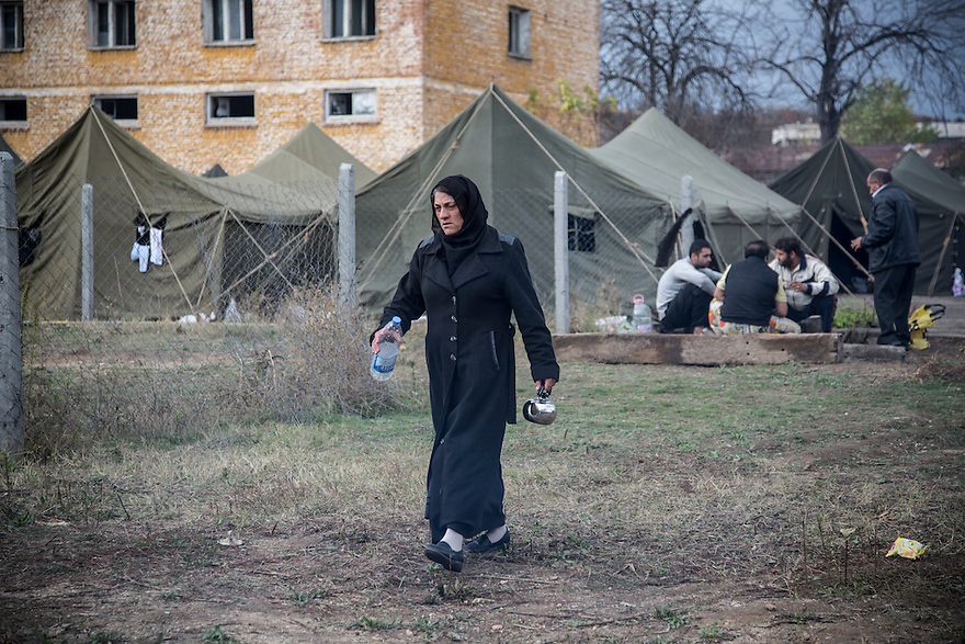 A Syrian woman going to get water for tea at Harmanli, a former military camp near the Turkish border. Beginning in 2013, officials placed refugees inside military tents with only dirt floors even during the winter months, when it was cold and damp and many people suffered from respiratory infections.