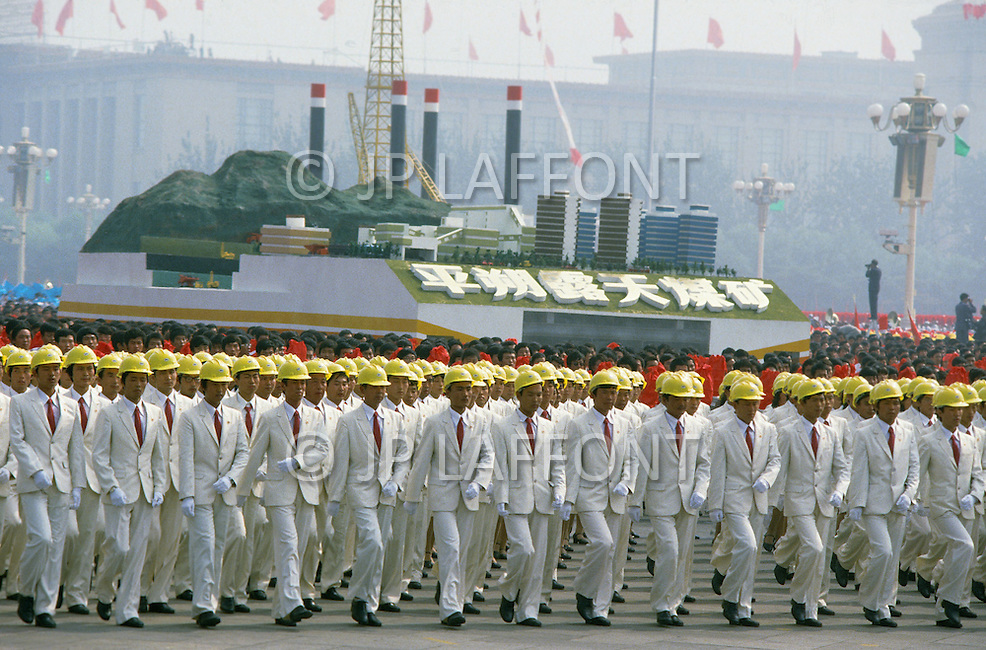1st October, 1984. Beijing, China. This huge parade is for the celebration of the 35th Anniversary of the Chinese Revolution. Float of a coal mining industry representing progress and research, walking along a huge crowd of engineers.