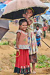 Rohingya refugee children share an umbrella as they walk though the sprawling Kutupalong Refugee Camp near Cox's Bazar, Bangladesh. More than 600,000 Rohingya refugees have fled government-sanctioned violence in Myanmar for safety in this and other camps in Bangladesh.