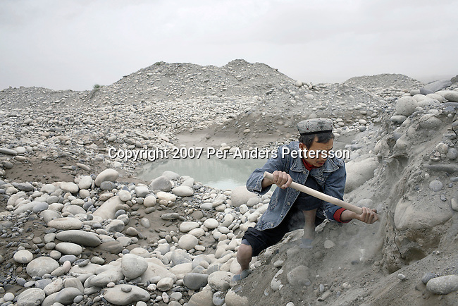 KHOTAN, CHINA - JUNE 17: A Jade digger looks for jade in the river bed on the White Jade River on June 17, 2007 in Khotan, China. Many people come to the river to try their luck. Many are farmers and they live difficult conditions in caves along the river. The jade from Khotan is well known and many traders and shops are based there. (Photo by Per-Anders Pettersson)...
