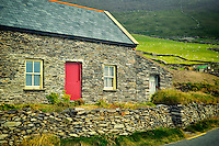Stone house and sheep in pasture with stone fences on Slea Head Drive. Dingle Peninsula, Ireland.