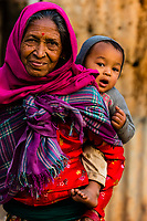 A grandmother carrying her grandson in the lower mountains of the Himalayas near Pokhara, Nepal.