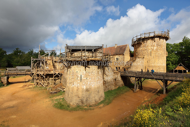 North Range or Logis Seigneurial in the centre, completed 2010, with the Great Tower or Tour Maitresse on the right, and Corner Tower in the centre, still under construction, lifting gear or squirrel cage with double drum, and footbridges over the moat trench, at the Chateau de Guedelon, a castle built since 1997 using only medieval materials and processes, photographed in 2017, in Treigny, Yonne, Burgundy, France. The Guedelon project was begun in 1997 by Michel Guyot, owner of the nearby Chateau de Saint-Fargeau, with architect Jacques Moulin. It is an educational and scientific project with the aim of understanding medieval building techniques and the chateau should be completed in the 2020s. Picture by Manuel Cohen