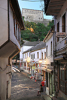 The Qafe or Neck of the Bazaar, a busy intersection of 5 streets that forms the heart of the old town of Gjirokastra, Southern Albania, with the Kalaja e Gjirokastres or Gjirokastra Castle above. Most of the Ottoman houses date from the 17th and 18th centuries. Gjirokastra was settled by the Greek Chaonians, the Romans and Byzantines before becoming an Ottoman city in 1417. Its old town was listed as a UNESCO World Heritage Site in 2005. Picture by Manuel Cohen