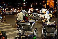 Street corner at night, with cyclos (bicycle rickshaws) standing waiting for customers. Ho Chi Minh City (Saigon), Vietnam