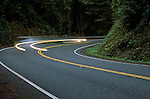 Highway 199 curving through Jedediah Smith Redwoods with car light streaks, two lane highway, Redwoods National Park Northern California near Crescent City, California State USA