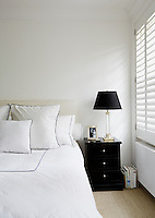 This contemporary bedroom is simply furnished with louvered shutters against the window