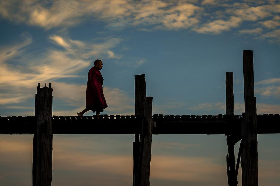 MANDALAY, MYANMAR - CIRCA DECEMBER 2013: Buddhist monk crossing the U Bein Bridge in Amarpura