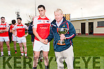 Muiris Ó Fiannachta, West Kerry GAA Chairperson, presenting the West Kerry Senior Championship cuap to Daingean U Chúis captain Breandan Ó Céilleachair at Pairc an Aghasaigh, Dingle, on Sunday afternoon.