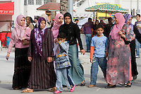 Tripoli, Libya, North Africa - Libyan Women and Children at International Trade Fair.  Clothing Styles.  Headscarves are worn by virtually all Libyan women from adolescence onward.  The shoulder-to-ankle-length abaya is favored by older women.  Denim is commonly used by younger women for skirts.  Children wear western European styles, including jeans and levis.