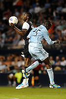 Shola Ameobi (black and white) Newcastle United controls the ball in the air despite the challenge of Danell Cyrus Sporting KC... Sporting Kansas City and Newcastle United played to a scoreless tie in an international friendly at LIVESTRONG Sporting Park, Kansas City, Kansas.