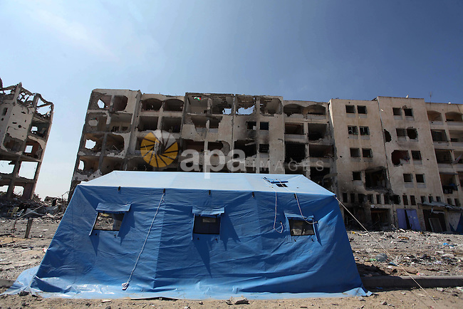 A picture taken on August 11, 2014 in Beit Lahia in the northern Gaza Strip shows a tent pitched in front of the destroyed Nada Towers as Palestinians return to the area to inspect what remains of their homes during a 72-hour ceasefire observed in the Gaza Strip. Almost 12 hours into the truce, the skies over Gaza remained calm, with no reports of violations on any side and signs of life emerging on the streets of the war-torn coastal enclave which is home to 1.8 million Palestinians. Photo by Ashraf Amra