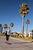USA, Los Angeles, a woman riding her skateboard on the Venice Boardwalk
