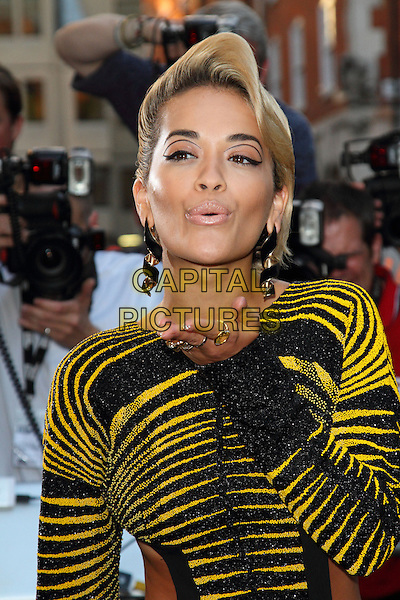 Rita Ora<br /> GQ Men of the Year Awards 2013 at the Royal Opera House, London, England.<br /> September 3rd, 2013<br /> half length yellow black dress cut out away sides stripe long sleeves  hand blowing kiss mouth open <br /> CAP/ROS<br /> &copy;Steve Ross/Capital Pictures