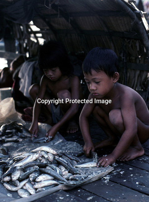 A poor fishing family on their boat on March 27, 1998 on the Tonle Sap river next to central Phnom Penh, Cambodia. The family lives on the boat and come to sell their catch at the central market everyday. .(Photo: Per-Anders Pettersson/ Liaison Agency)