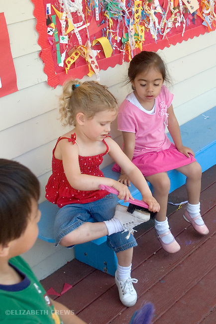 Berkeley CA Preschool girl cleaning sand off shoes before entering classroom, friend observing