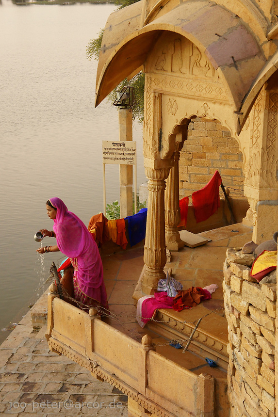 womans morning toilette on balcony at Gadi Sagar lake in Jaislamer city, Rajastan, India