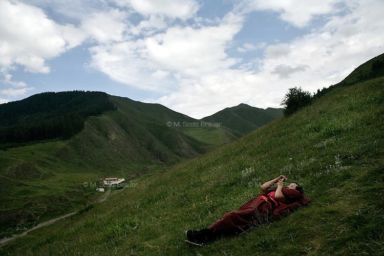 Tibetan Buddhist monks rest among the trees and hills surrounding the Labrang Monastery in Xiahe, Gansu, China.  Xiahe, home of the Labrang Monastery, is an important site for Tibetan Buddhists.  The population of the town is divided between ethnic Tibetans, Muslims, and Han Chinese.