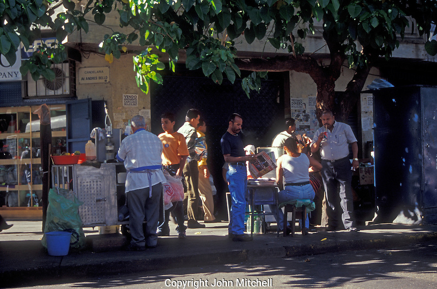 People drinking juice and talking on a street corner in downtown Caracas, Venezuela