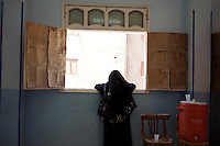 A woman wearing a black niqab stands at a window of the school in Al Saf village where the Muslim Sisters organized a meeting to talk with people about Mohamed Morsi's campaign. Egypt, June 2012.