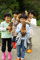 Four sisters hold bamboo shoots they have dug at Yamaguchi farm, Otaki, Chiba prefecture, Japan, April 29, 2011.
