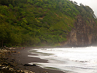 A group of hikers walk across the black sand beach of Pololu Valley, Big Island.