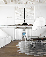 The dining area is demarcated by an inlaid floor of hexagonal-shaped ceramic tiles and the table is made of Swamp Kauri, a rare prehistoric wood