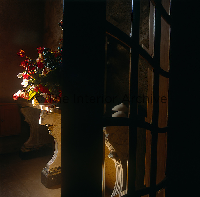 A view through a glazed door to a flower arrangement placed on a stone table.
