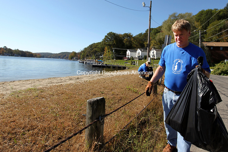 Winsted, CT- 09, October 2011-100911CM01  Jim Corthouts, of Canton picks up litter along Highland Lake in Winsted Sunday morning.  Corthouts was among a group of volunteers who spent the warm Fall day picking up litter around the lake.  Corthouts said he recently purchased a summer home on the lake, and was participating in annual event for the first time.  Behind Corthouts, is volunteer, Cynde Grogan, of Brookfield.  The clean up was organized by  the Highland Lake Watershed Association.  Christopher Massa Republican-American