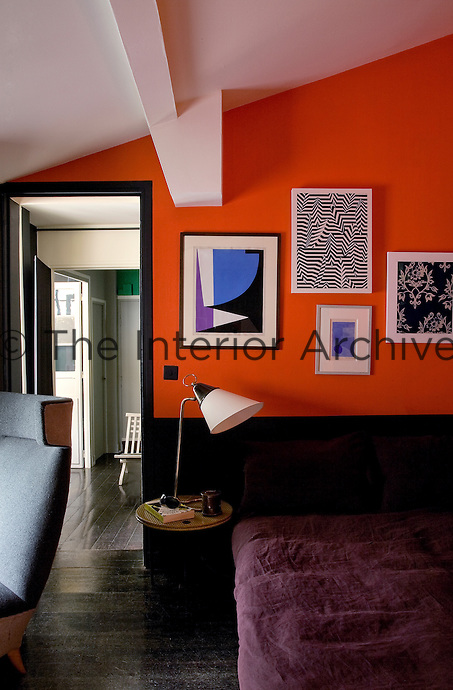 Acollection of prints hangs above the bed in the master bedroom against a backdrop of intense orange