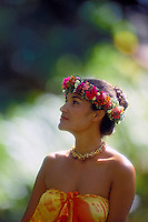 Side view of beautiful Polynesian woman with upswept hair framed by red and white haku-lei, wearing yellow and orange pareo against out of focus background of green foliage.