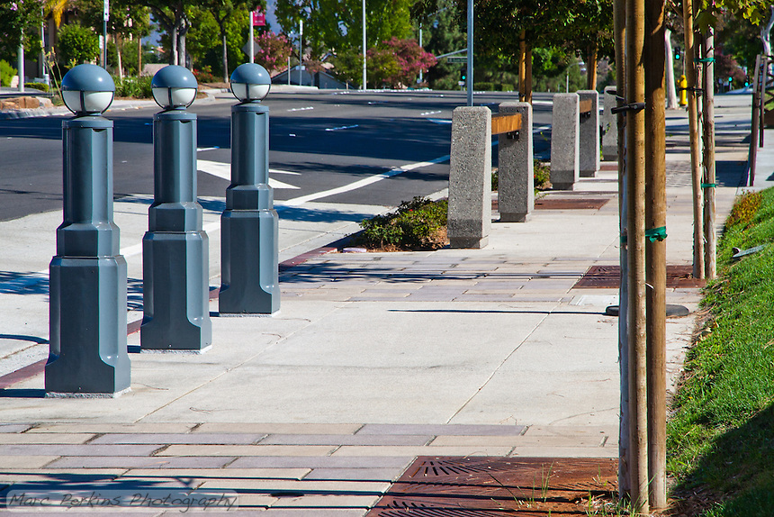 """Three blue-gray metal lights (that remind me of little soldiers in a row) stand at the bus stop on the northeastern corner of Gand and Diamond Bar.  The parkway treatment is also visible.  This was part of the 2015 rebuild of the Grand Avenue and Diamond Bar Boulevard intersection for Diamond Bar's 2015 """"Grand Avenue Beautification"""" project, landscape architecture for the project was by David Volz Design."""