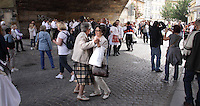 People enjoying themselves and dancing to the traditional music being played under Charles Bridge in Prague, during The ride of Kings in May 2015.<br /> <br /> Pilgrims from around the world traditionally come to Prague to honour Saint John of Nepomuk.<br /> Venetian gondoliers come to Prague every year for this celebration. Saint John of Nepomuk is the patron of all gondoliers and one of the eight patrons of Venice. The statue of Saint John of Nepomuk is the only Baroque statue situated right on the bank of the Grand Canal in Venice, Italy.<br /> <br /> Twelve-year-old Frantisek Libosvar dressed as a girl and with a rose in his mouth leads the royal procession during Ride of the Kings as part of Navalis Celebrations on May 15, 2015 in Prague, Czech Republic. The Navalis Saint John's celebrations take place to commemorate Czech saint and Prague native, Saint John of Nepomuk, patron of all people of the water. <br /> <br /> <br /> The Ride of the Kings takes place during the spring, as a part of the Pentecost traditions . A group of young men ride through a Prague in a ceremonial procession. The ride is headed by chanters, followed by pageboys with unsheathed sabres who guard the King &ndash; a young boy with his face partially covered, holding a rose in his mouth &ndash; and the rest of the royal cavalcade. The King and pageboys are dressed in women&rsquo;s ceremonial costumes, while the other riders are dressed as men. The entourage rides on decorated horses, stopping to chant short rhymes that comment humorously on the character and conduct of spectators. The chanters receive donations for their performance, placed either in a money box or directly into the riders&rsquo; boots. The King&rsquo;s retinue returns home after a few hours of riding, and celebrates in the evening at the house of the King with a small feast, music and dancing. The practices and responsibilities of the Ride of the Kings are transmitted from generation to generation. The traditional paper decorations for the horses and the ceremonial costumes, in particular