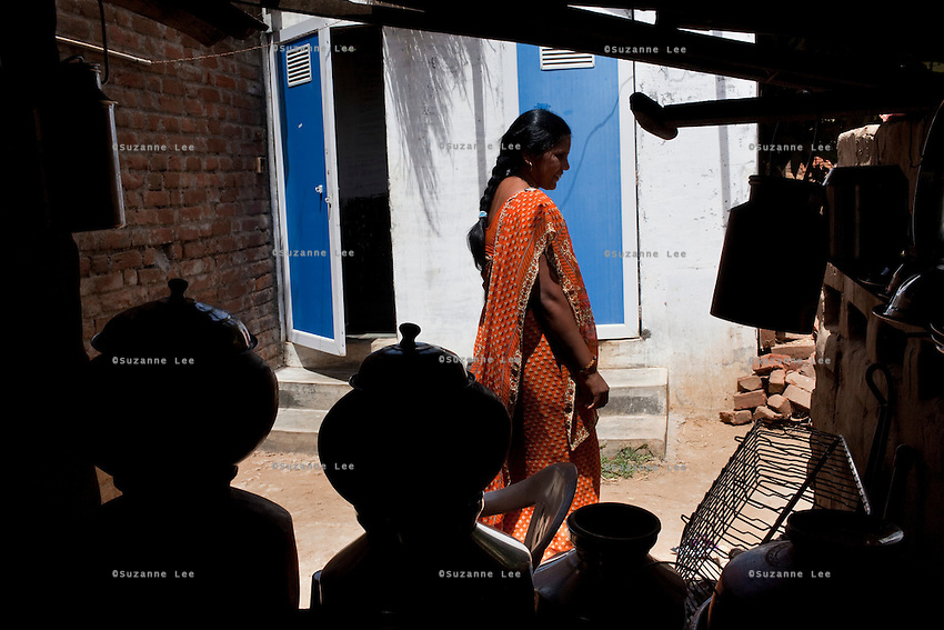 "Shardaben walks around the back of her house where she used the surrogacy money to build two toilets...Shardaben Kantiben, 31; Husband is Kantibhai Motibhai (37).3 children --- 2 girls -  Usha(15) and Lakshmi (18, in pink); 1 boy, Chintan (17).- Education costs for all three come to Rs. 15,000 per year.- Shardaben was a two-time surrogate. First time she gave birth to twin girls for a Taiwanese couple and the second time a boy for an Indian couple from America (photo on TV set because she's proud that it was a boy).- The second time she became emotional and they got a gold ring of Rs. 1,500 made for the boy, which they presented to the biological parents. They are not in touch with either couple..- From the two surrogacies, they earned a little over 700,000rupees..-200,000rupees will be given as dowry for Lakshmi's wedding..- They leased agricultural land (Rs. 2 lakhs for five years) which earns them Rs. 60,000-70,000 a year; they bought two buffaloes worth Rs. 60,000 and make almost 6000-7000 per month selling milk; they bought a motorbike for Rs. 25,000; they put some money into house repairs and the construction of toilets, and opened a fixed deposit in Shardaben's name for Rs. 1.5 lakh and one in the name of their son, Chintan, for Rs. 25,000..Quotes..""Everyone says they'll keep in touch and take down addresses and phone numbers but nobody looks back. And I guess it works well. Our main interest was in the money. Their main interest is in the baby."" - KantiBhai.""Their rules apply at the surrogate house. It does curtail the freedom. When I used to go, everybody would just be lying. They count the days when they can go back."" - Kantibhai.""Ours is natural birth but surrogacy is a man-made pregnancy. There's a lot of risk. She must have taken at least 300 injections."" - Kantibhai of his wife...The Akanksha Infertility Clinic is known internationally for its surrogacy program and currently has over a hundred surrogate mothers pregnant in their environmentally control"