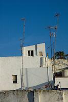 Crooked TV Aerials on rooftops at sunrise, Tarifa, Andalusia, Spain.