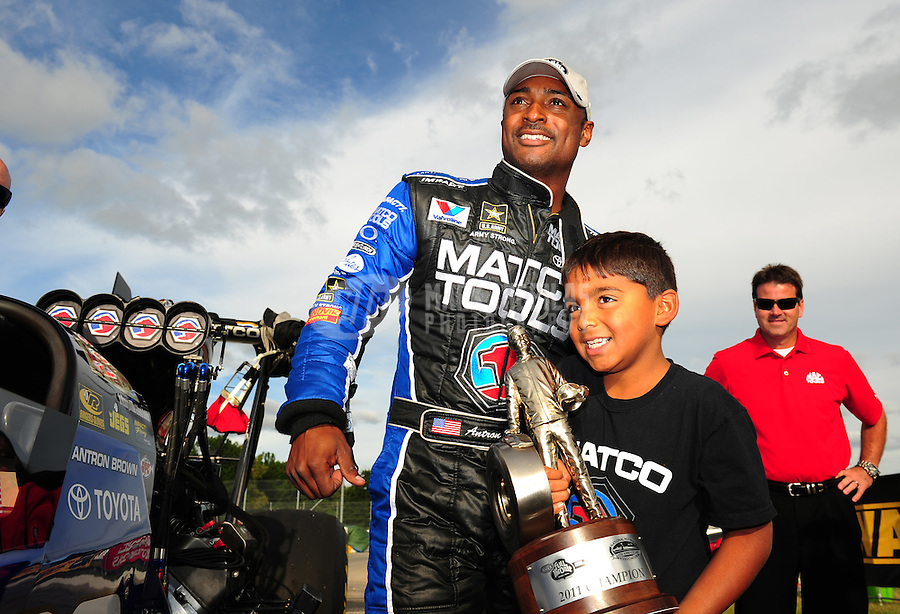 Sept. 5, 2011; Claremont, IN, USA: NHRA top fuel dragster driver Antron Brown celebrates with son Anson Brown after winning the US Nationals at Lucas Oil Raceway. Mandatory Credit: Mark J. Rebilas-
