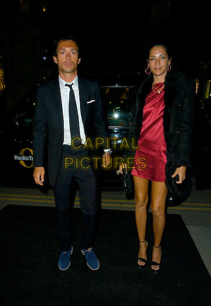 DAN McMILLIAN & ASTRID MUNOZ.The Sergio Rossi store launch party, Sloane Street, London, England..April 4th, 2007.full length black suit red dress satin coat blue shoes .CAP/CAN.©Can Nguyen/Capital Pictures
