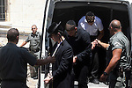 A few of the 57 Ultra-Orthodox Jews who were arrested in the Sabbath riots are seen covering their faces as they are brought to their arraignment in the Hashalom court in Jerusalem, Sunday, June 28, 2009. The detainees were arrested during the violent clashes with police on Saturday, June 27, when a few thousand Ultra-Orthodox Jews took to the streets to protest the opening of one of Jerusalem's parking lot on the Jewish Sabbath. The demonstrators clashed with police forces, and hurled garbage, glass and stones at police and at members of the press. Photo By: Tess Scheflan / JINI