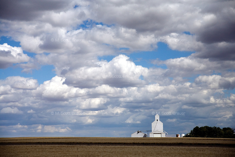 A grain elevator stands on the horizon on a cloudy day outside of Great Falls, Montana, USA.