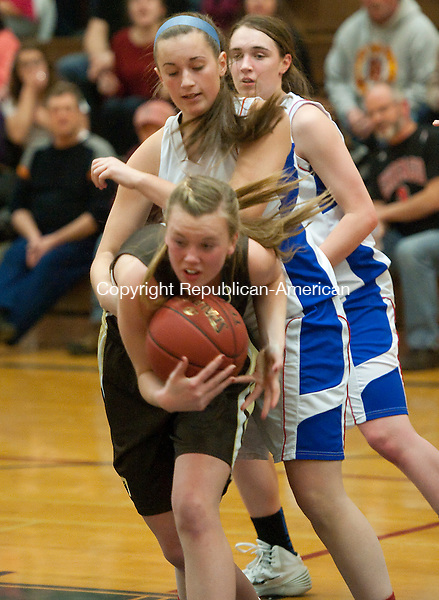 WOODBURY, CT-010714JS08-Thomaston's Gabriel Hurburt (11) grabs a loose ball in front of Nonnewaug's Allison Charette (15) during their game Tuesday at Nonnewaug High School in Woodbury. <br /> Jim Shannon Republican-American