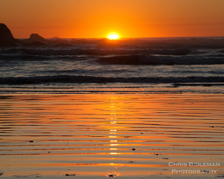 Sunset on the Oregon Coast at low tide causing ripples in the sand.  Light from sun causes great shadow effect.